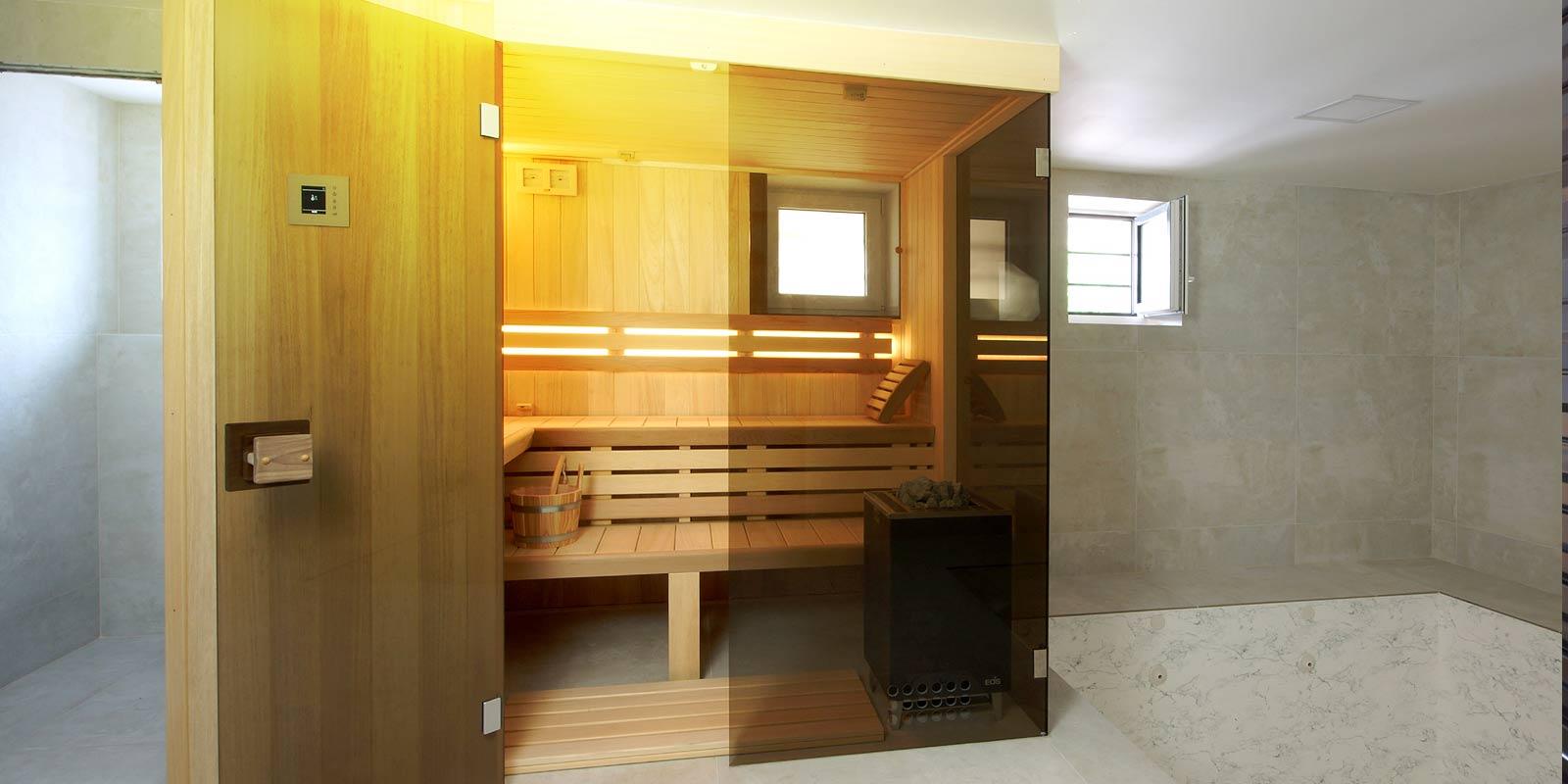 Finská sauna Modus s prosklenou čelní stěnou a obkladem ze dřeva abachi